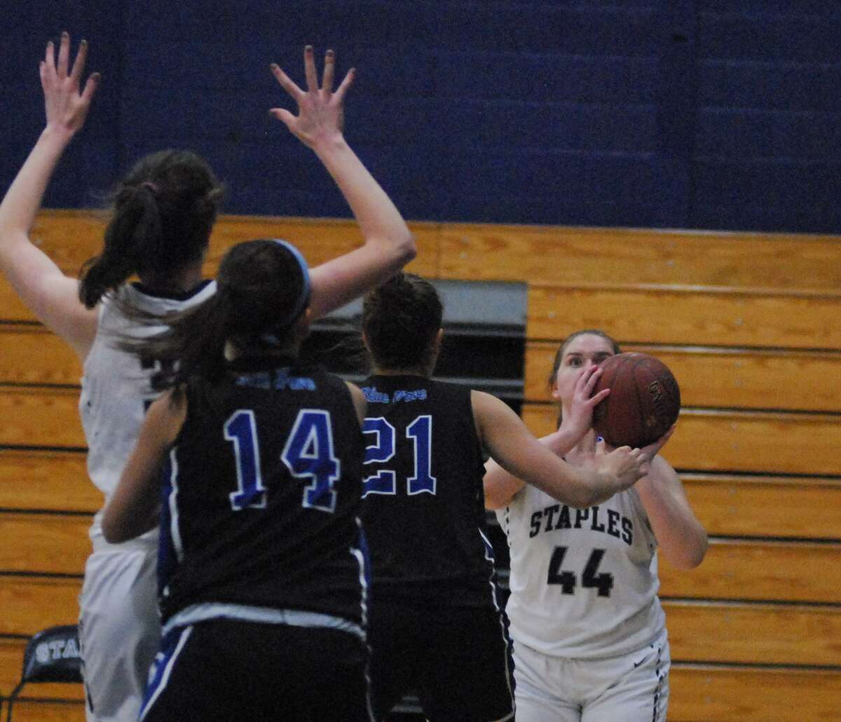 Staples' Julia Brower, right, takes a shot during a game against Darien on Tuesday.