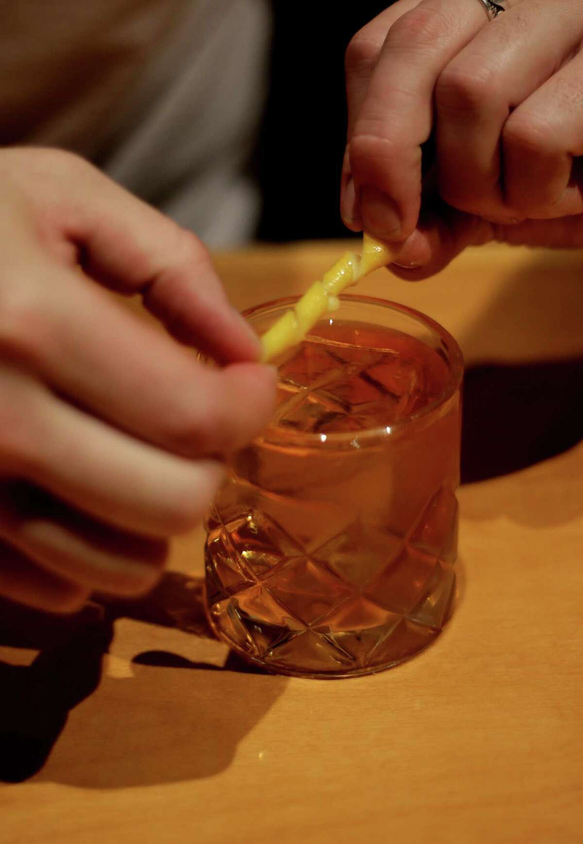 Peter Jahnke adds a lemon twist to a Rusty Nail at Tongue-Cut Sparrow, 310 Main, in downtown Houston.
