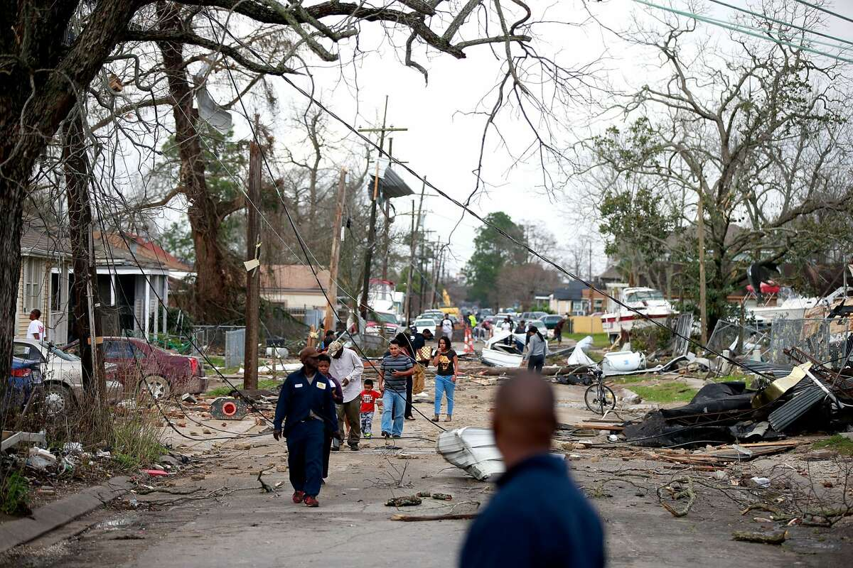 Residents walk down a street along Chef Menture Ave after a tornado touched down in the eastern part of the city on February 7, 2017 in New Orleans, Louisiana. According to the weather service 25 people were injured in the aftermath of the tornado.