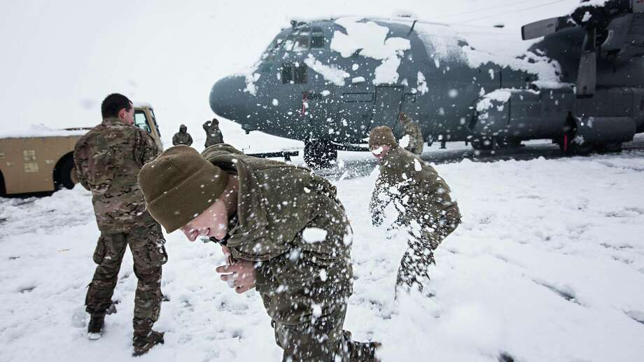 Members of the 455th Expeditionary Aircraft Maintenance Squadron EC-130 Compass Call Aircraft Maintenance Unit have a snowball fight after shoveling snow from under their aircraft at Bagram Airfield, Afghanistan Feb. 4, 2017. The unit ensured their aircraft were cleared of snow to return to the mission after the base got several inches of snowfall. Photo: Courtesy/U.S. Air Force Photo By Staff Sgt. Katherine Spessa