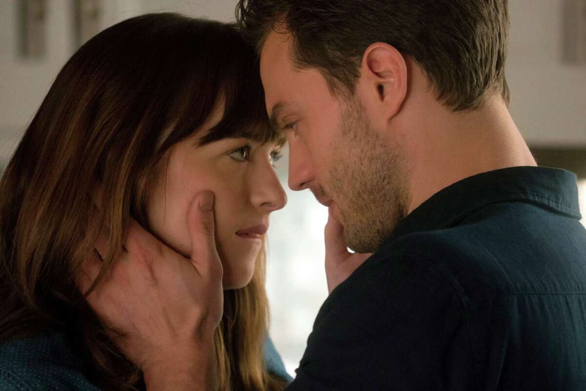 """This image released by Universal Pictures shows Dakota Johnson as Anastasia Steele, left, and Jamie Dornan as Christian Grey in """"Fifty Shades Darker."""" (Doane Gregory/Universal Pictures via AP)"""