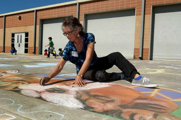 Local artist Carol Wells, a 1976 graduate of Klein High School, leads Greenwood Forest Elementary students in their Paint the Community with Peace chalk masterpiece on the school's basketball court playground on Feb. 11, 2016.(Photo by Jerry Baker/Freelance)