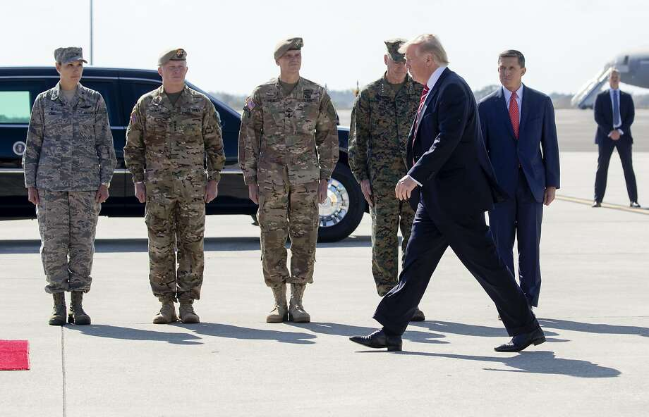 President Donald Trump is greeted by National Security Adviser Michael Flynn, right, and members of the military at MacDill Air Force Base in Tampa, Fla., Feb. 6, 2017. Photo: STEPHEN CROWLEY, NYT