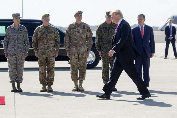 FILE — President Donald Trump is greeted by National Security Adviser Michael Flynn, right, and members of the military at MacDill Air Force Base in Tampa, Fla., Feb. 6, 2017. Policy experts and retired officers complained Tuesday that Trump sent the wrong signal to the military by opening his remarks here on Monday with a campaign-style celebration of his election victory. Third left is Gen. Joseph Votel, who leads United States Central Command. (Stephen Crowley/The New York Times)