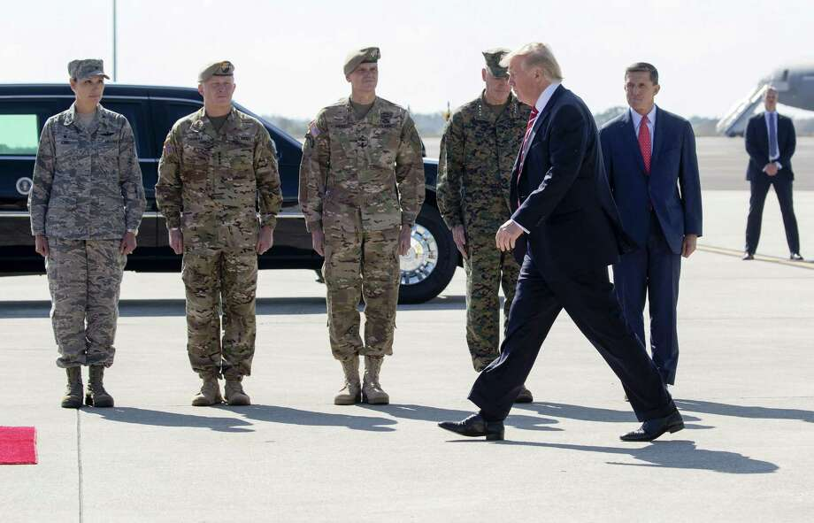 FILE — President Donald Trump is greeted by National Security Adviser Michael Flynn, right, and members of the military at MacDill Air Force Base in Tampa, Fla., Feb. 6, 2017. Policy experts and retired officers complained Tuesday that Trump sent the wrong signal to the military by opening his remarks here on Monday with a campaign-style celebration of his election victory. Third left is Gen. Joseph Votel, who leads United States Central Command. (Stephen Crowley/The New York Times) Photo: STEPHEN CROWLEY, STF / NYT / NYTNS