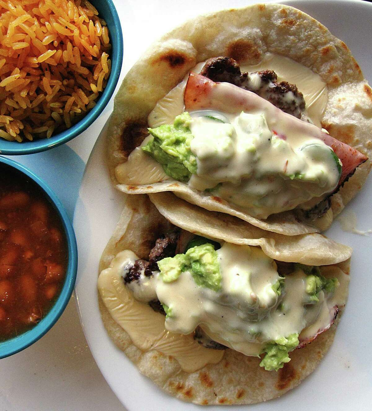 Mexican cheeseburger tacos with ground beef, grilled ham, queso, avocado and jalapeños, served with rice and beans, from Chisme.