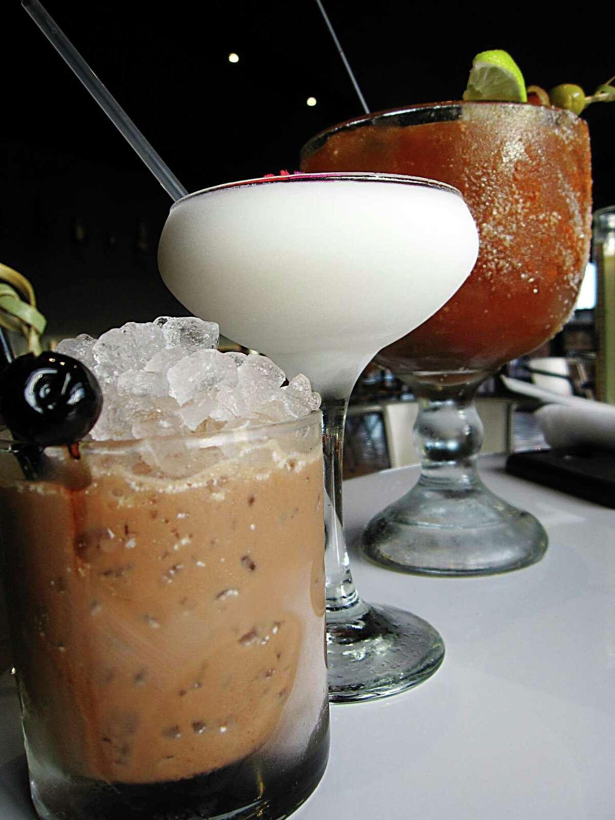 Cocktails from Chisme. From left: Chorreado with scotch and mole, Chismosa with cachaca and coconut and a 32-ounce michelada.