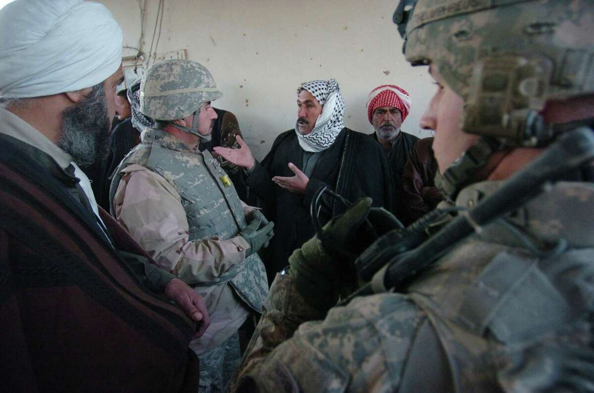 In this 2008 photo, an Iraqi man asks an an interpreter working for the U.S. military a question as as Army troops begin to set up a U.S.-funded Sunni militia to defend against al-Qaida.
