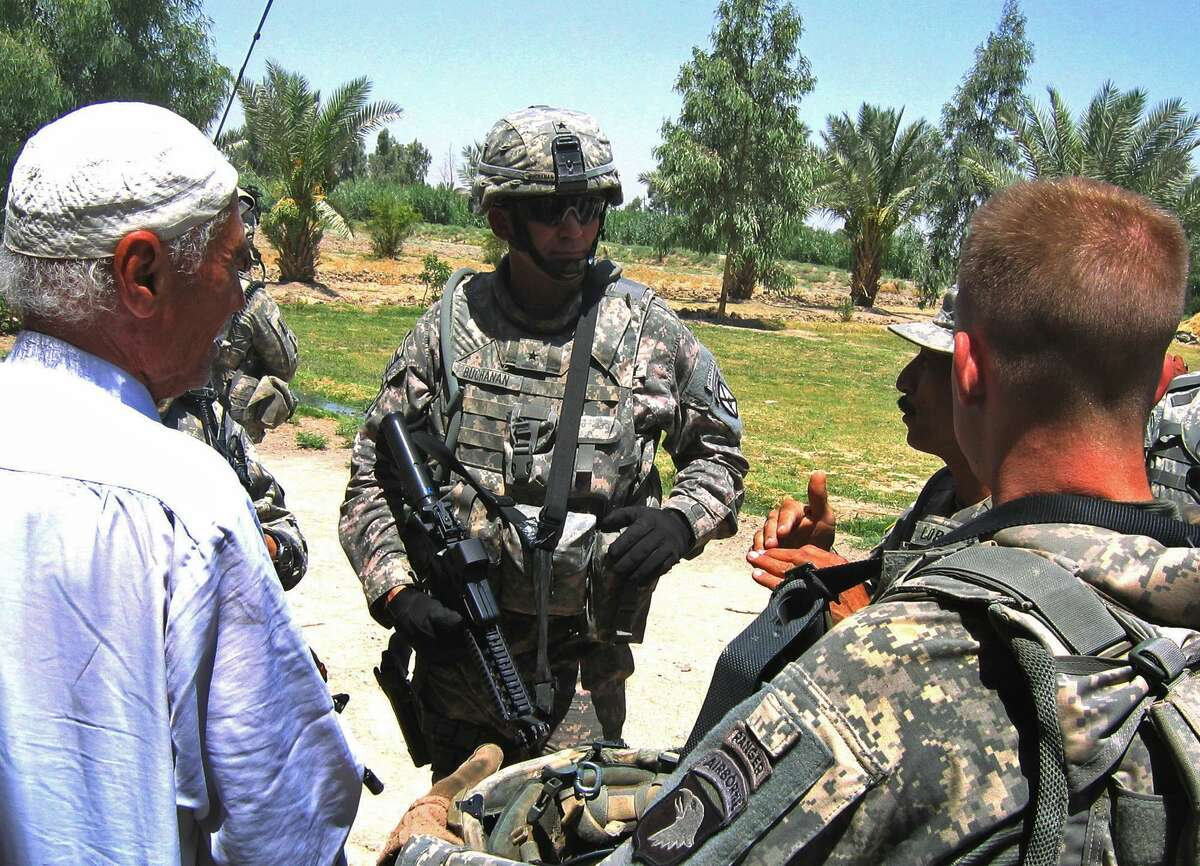 Capt. George Morris, right, foreground, and Brig. Gen. Jeffrey Buchanan, center, speak through an interpreter to an Iraqi chicken farmer, left, in a once-violent stretch of farm country south of Baghdad Tuesday, July 15, 2008. (AP Photo/Robert Burns)