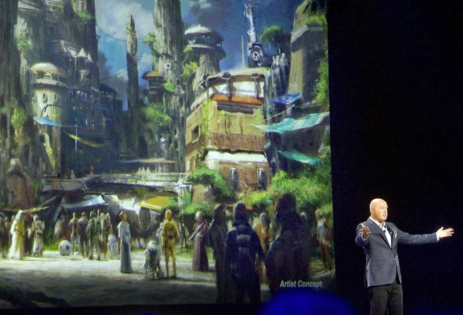 FILE - In this Saturday, Aug. 15, 2015, file photo, Bob Chapek, chairman of Walt Disney Parks and Resorts, speaks in front of concept art of the newly announced Star Wars Land at the D23 Expo in Anaheim, Calif. Disney CEO Bob Iger said Tuesday, Feb. 7, 2017, the company will open its Star Wars-themed lands at California's Disneyland and Florida's Walt Disney World in 2019.>> Click through the gallery to see concept art of Star Wars Land. Photo: Mindy Schauer, Associated Press