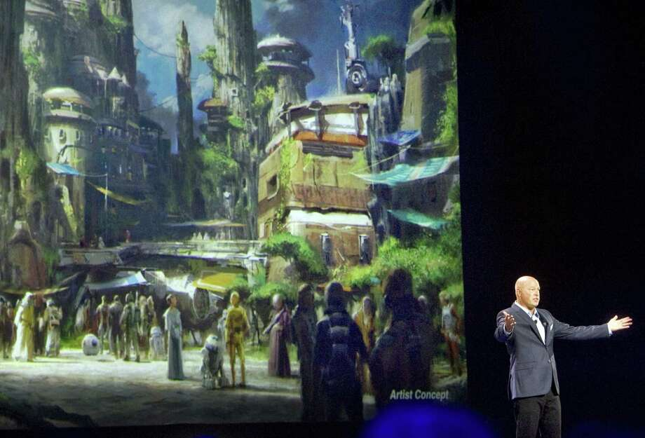 Bob Chapek, chairman of Walt Disney Parks and Resorts, speaks in front of concept art of the newly announced Star Wars Land at a 2015 expo. Disney CEO Bob Iger says the company will open its Star Wars-themed lands at California's Disneyland and Florida's Walt Disney World in 2019. Photo: Associated Press /File Photo / The Orange County Register