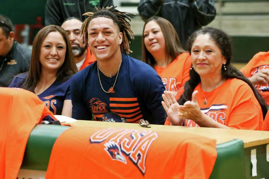 Southwest's Robert Fuentes smiles after signing his letter of intent to play football at UTSA in the Southwest gym seated next to his grandmother, Evelyn Moreno (right) and his mother, Iliana Estrada, on Wednesday, Feb. 1, 2017. MARVIN PFEIFFER/ mpfeiffer@express-news.net Photo: Marvin Pfeiffer /San Antonio Express-News / Express-News 2017