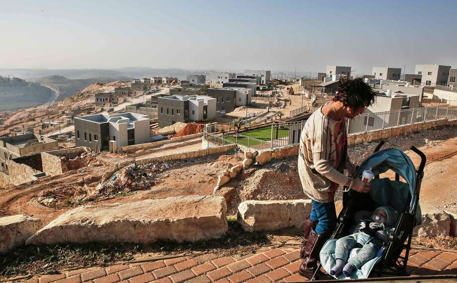 An Israeli woman feeds her baby near a settlement project close to the West Bank city of Ramallah. Photo: GIL COHEN-MAGEN, AFP/Getty Images