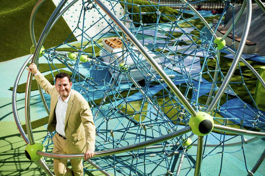 """Levy Park director Doug Overman poses for a portrait in the """"Cosmo,"""" a buckyball inspired climbing attraction in the children's play area. Photo: Brett Coomer, Staff / © 2017 Houston Chronicle"""