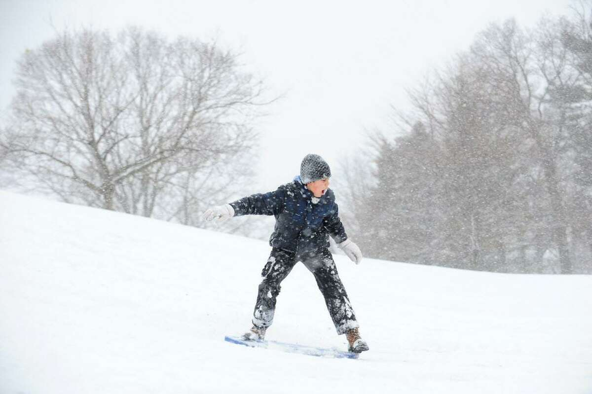 FILE - Twelve-year old Chase Caruso snowboards down a hill at Cummings Park on Monday, Feb. 8, 2016 after Stamford schools had a snow-related early dismissal.