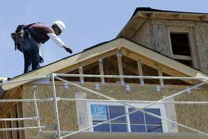 In this Sept. 16, 2010 photo, a roofer works on a Toll Brothers homes under construction in Sunnyvale, Calif. Housing construction surges 10.5 percent in August, as applications for building permits rise.(AP Photo/Paul Sakuma)