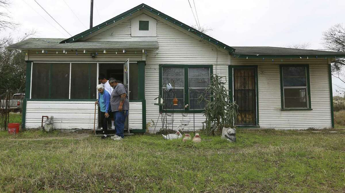 Crisanta Torres, is helped out of her home by her grandson Ray Torres, Jr and her son Richard Torres, Jr. The Torres family has turned down several offers from Lifshutz to buy the property, which they say has been in the family for more than 150 years.