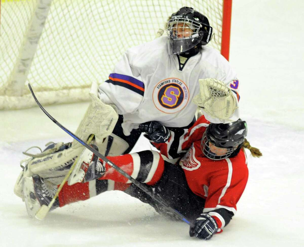 Branford Emma Sheehan (14) is called for interference after colliding with Stamford-Westhill-Staples goalie Mary Leydon (30) in the second period of a varsity girls hockey game at Terry Conners Rink in Stamford on Feb. 8, 2017. Branford defeated Stamford-Westhill-Staples 3-0.