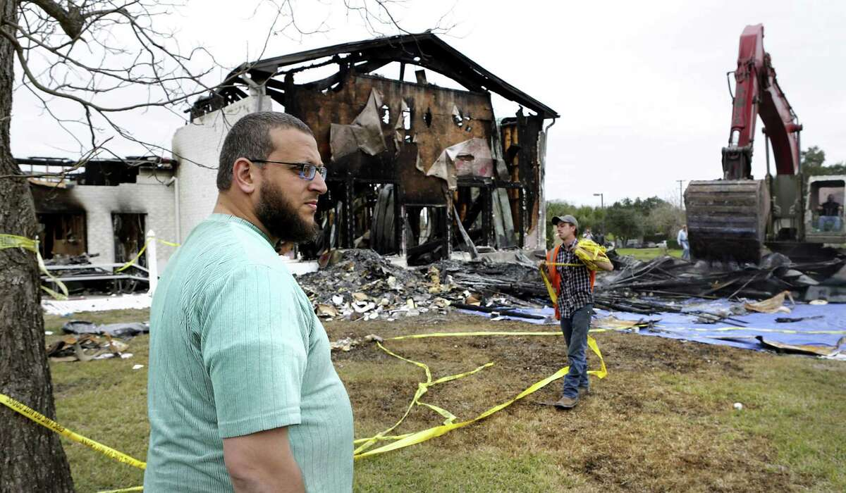 Imam Osama Hassan looks over the total loss of the Victoria Islamic Center, in Victoria, Texas on Tuesday, Feb. 2, 2017, as workers from Axis Demolition prepare to tear down the damaged mosque.