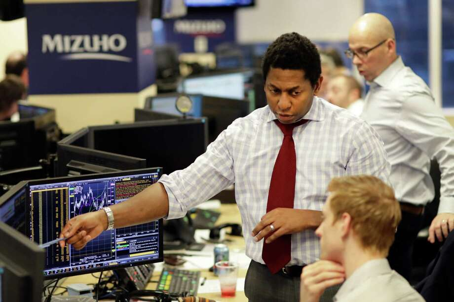 Traders work on the Mizuho Americas trading floor in New York. Wednesday was a mixed day on Wall Street, though the Nasdaq had a record high. Photo: Mark Lennihan, STF / Copyright 2017 The Associated Press. All rights reserved.