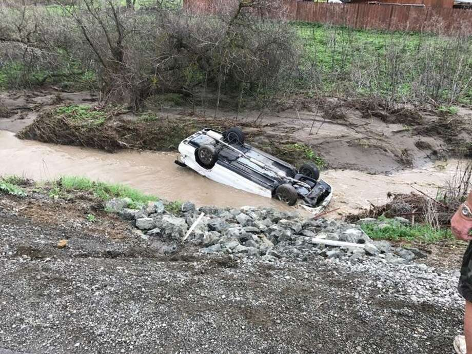 Two ranchers came to the rescue of the 20-year-old driver of this Toyota Corolla after the vehicle skidded off a road near Livermore Tuesday and landed upside down in a creek. Photo: California Highway Patrol / /