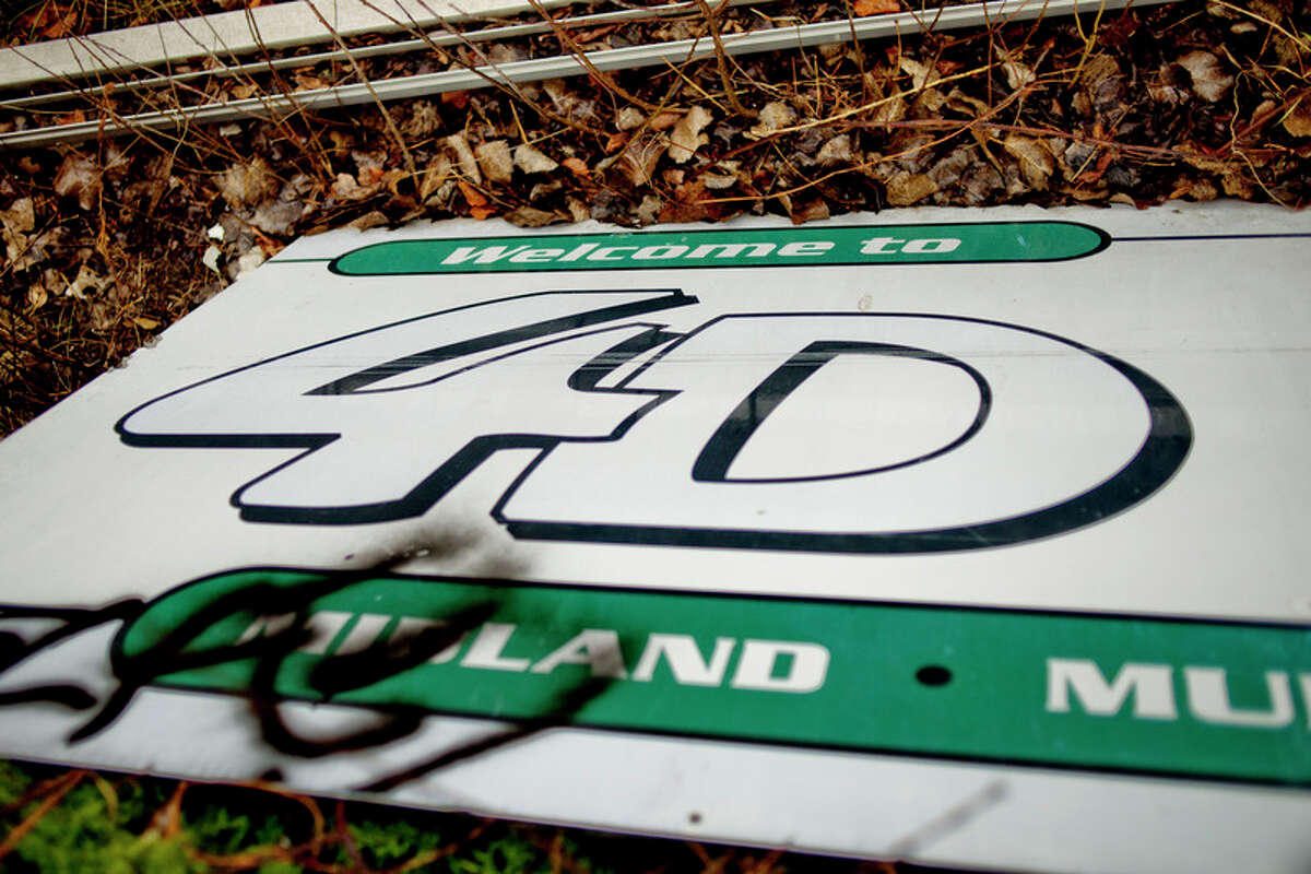 An old sign rests upside down on the ground at the former 4D site at 426 River Road in this 2015 file photo.
