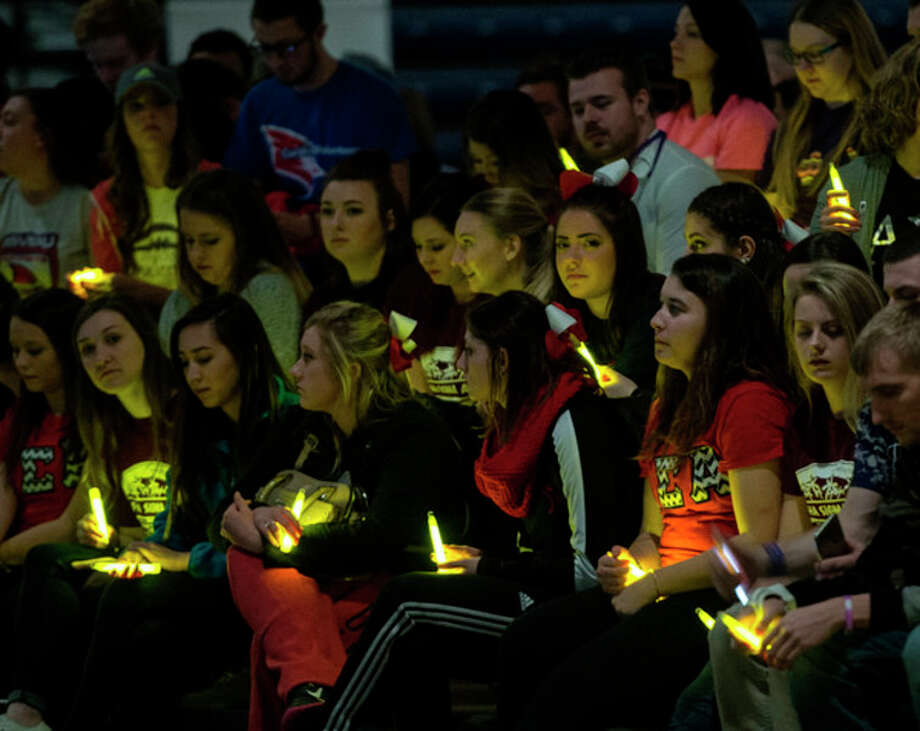 Mike Randolph, SVSU Saginaw Valley State University students hold glow sticks during a moment of remembrance during the Relay for Life event at SVSU Feb. 26, 2016.