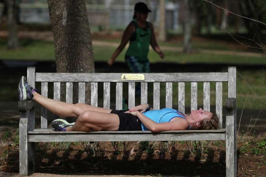 Dallas resident Suzann Robinson took a 20-minute nap between running the Memorial Park loop and waiting on a friend to walk another lap Wednesday. The high hit a record 85 degrees. Photo: Steve Gonzales, Staff / © 2017 Houston Chronicle