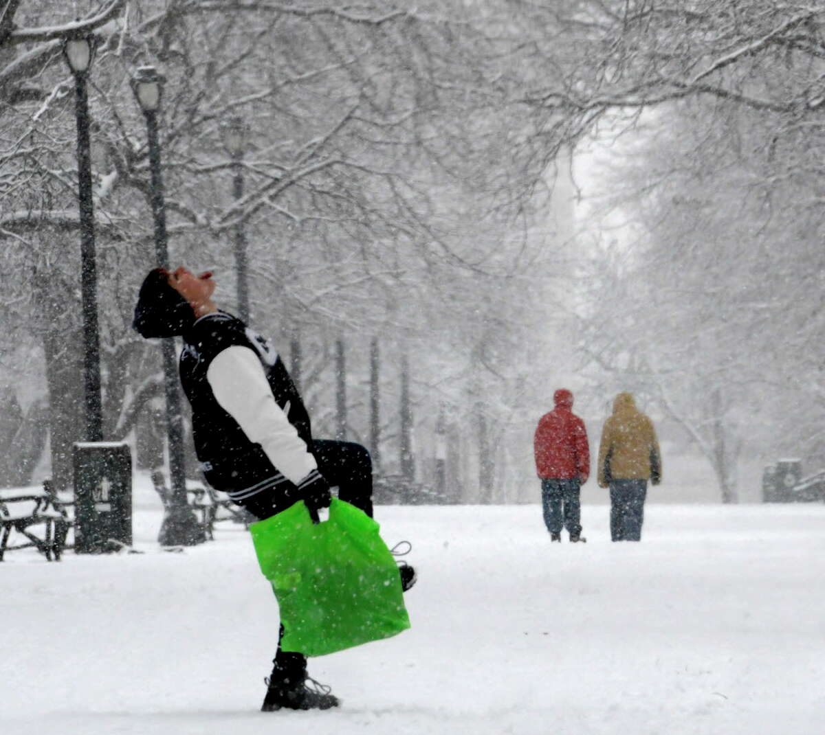 The Capital Region will get a taste of winter weather Thursday when the remnants of Hurriane Zeta move in and drop the first measurable snow of the fall. In this photograph, Alycia Johnson-Dardiz  of Albany tries catching snowflakes as she walks through Washington Park on Thursday, Dec. 29, 2016, in Albany N.Y. (Skip Dickstein/Times Union)