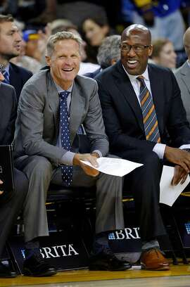 Golden State Warriors' head coach Steve Kerr and assistant coach Mike Brown enjoy a Stephen Curry 3-pointer in 2nd quarter against New Orleans Pelicans during NBA game at Oracle Arena in Oakland, Calif., on Monday, November 7, 2016.