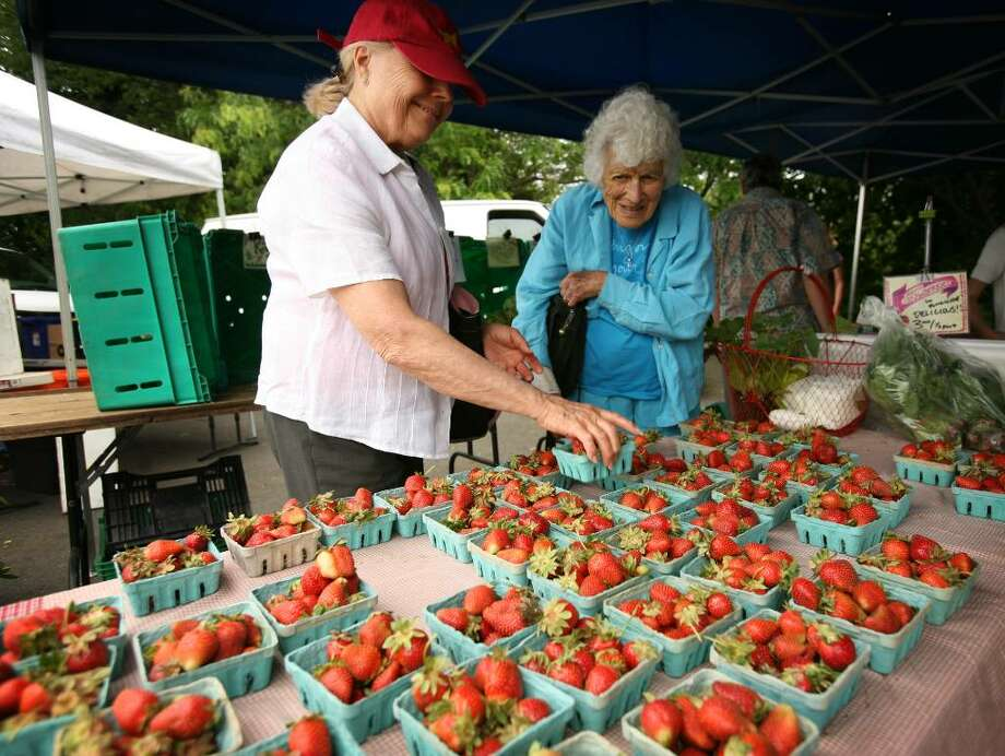 Johanna Gencarella, left of Greenwich, and Peggy Rabut of Westport shop for fresh strawberries on the opening day of the Westport Farmers Market on Thursday, May 27, 2010. Photo: Brian A. Pounds / Connecticut Post