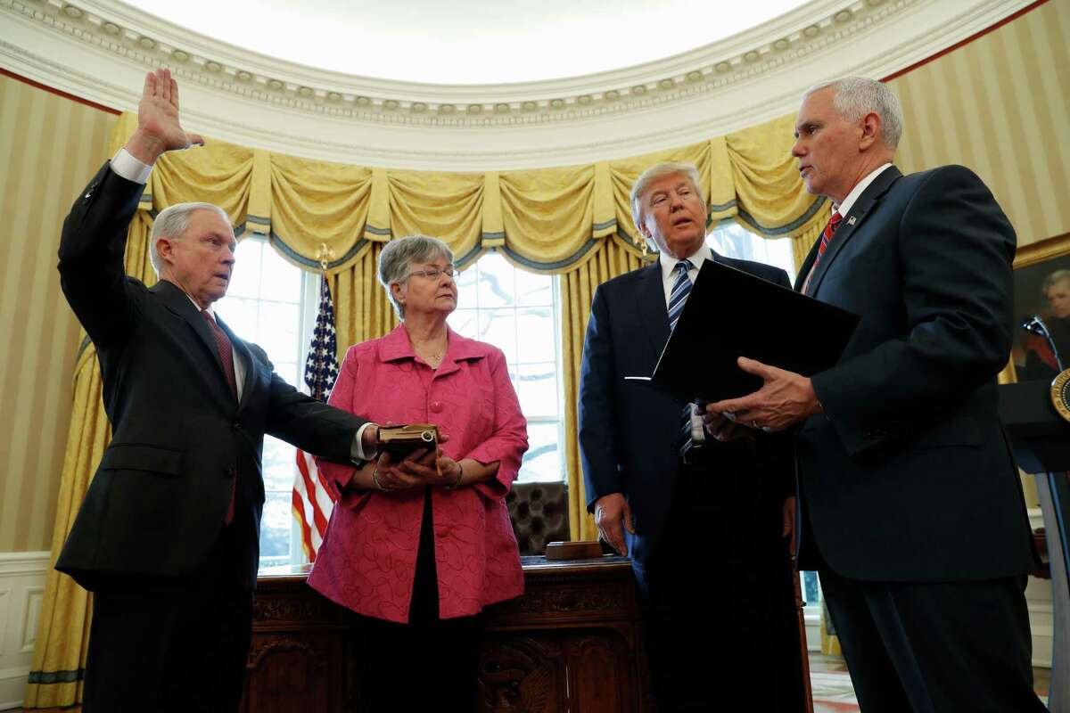 President Donald Trump watches as Vice President Mike Pence administers the oath of office to Attorney General Jeff Sessions, accompanied by his wife Mary, Thursday, Feb. 9, 2017, in the Oval Office of the White House in Washington.