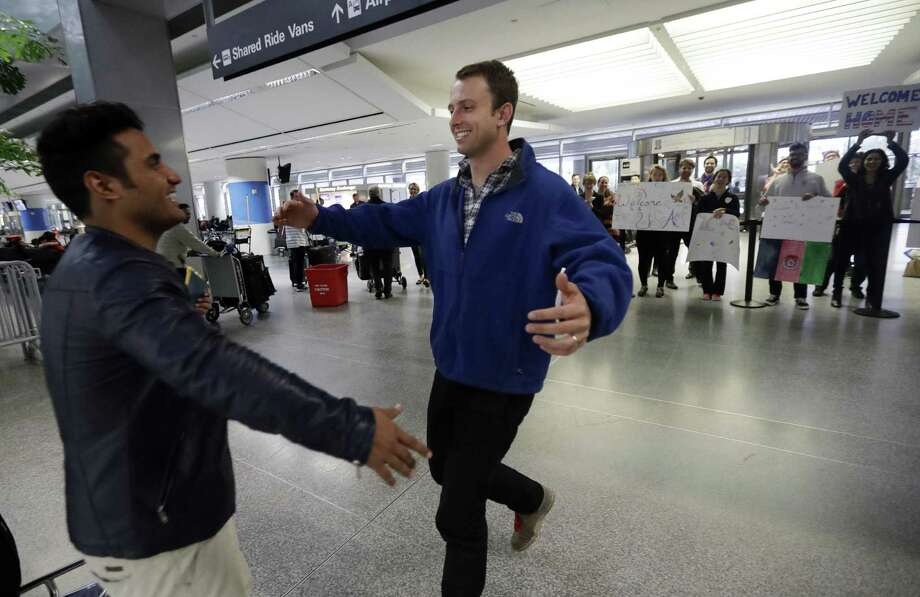 Army Capt. Matthew Ball, right, prepares to hug his former interpreter Qismat Amin, as Amin arrives from Afghanistan, at San Francisco International Airport Wednesday, Feb. 8, 2017, in San Francisco. Ball welcomed Amin to the United States after buying him a plane ticket to ensure he would get in quickly amid concerns the Trump administration may expand its travel ban to Afghanistan. (AP Photo/Marcio Jose Sanchez) Photo: Marcio Jose Sanchez, STF / Associated Press / Copyright 2017 The Associated Press. All rights reserved.