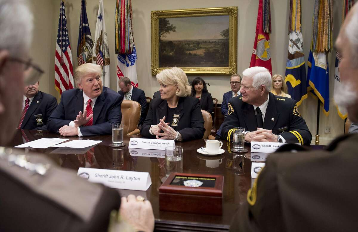 FILE: US President Donald Trump speaks alongside Sheriff Carolyn Bunny Welsh (C), of Chester County, Pennsylvania, and Sheriff Harold Eavenson (R), of Rockwall County, Texas, during a meeting with county sheriffs in the Roosevelt Room of the White House in Washington, DC, February 7, 2017.