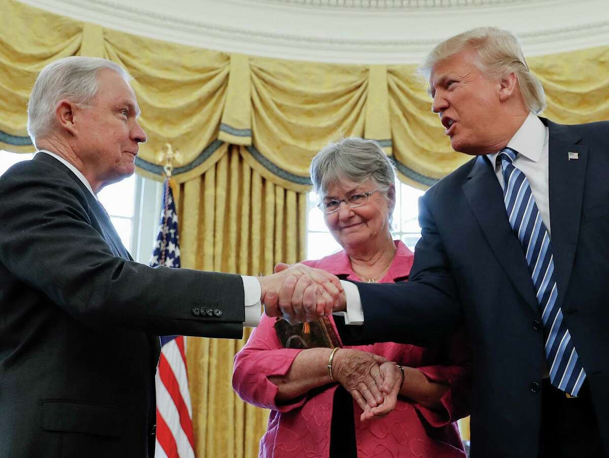President Donald Trump shakes hands with Attorney General Jeff Sessions, accompanied by his wife Mary, after he was sworn-in by Vice President Mike Pence, Thursday, Feb. 9, 2017, in the Oval Office of the White House in Washington.