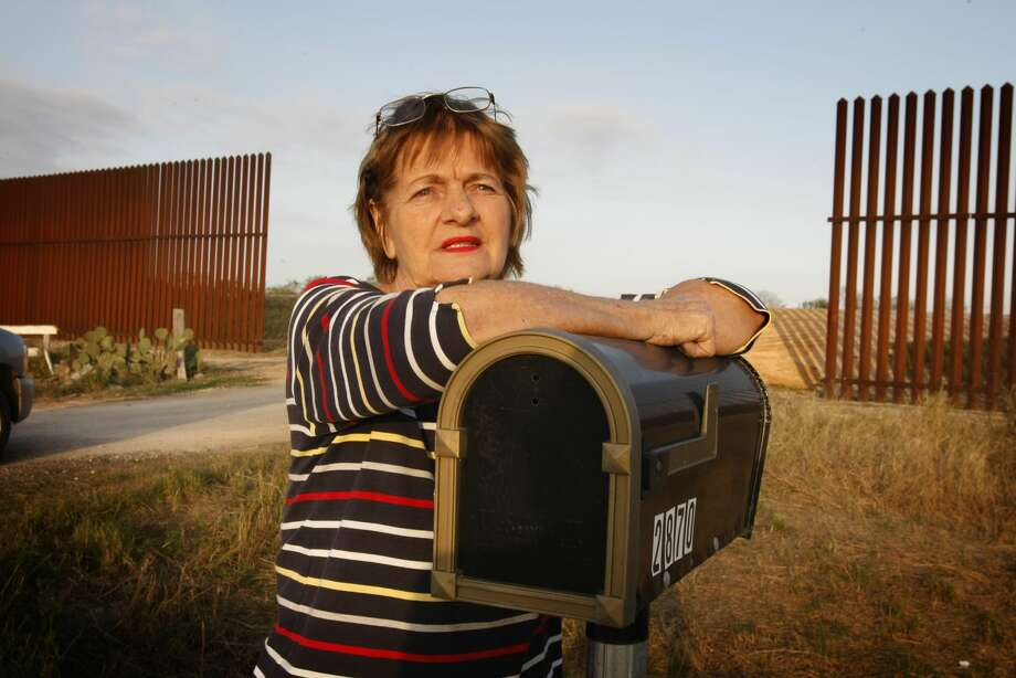 "FILE-- In this Jan. 19, 2011 file photo on Farm Road 1419 outside of Brownsville, Texas, Debbie Loop stands at the recently constructed high U.S./Mexico border fence that chops her property in half and divides her family's residences. Her house, equipment maintenance shop and fruit stand are now on this side of the fence and her son's homes and groves are on the south side. The temporary gap in the barrier behind her allows access but will eventually be closed with a huge, electrically operated gate. ""I can't take it anymore,"" she says of the division and the condemnation of her land and the $1000's she and her family wasted on the legal battle with the U.S. government.  Photo: Don Bartletti/LA Times Via Getty Images"