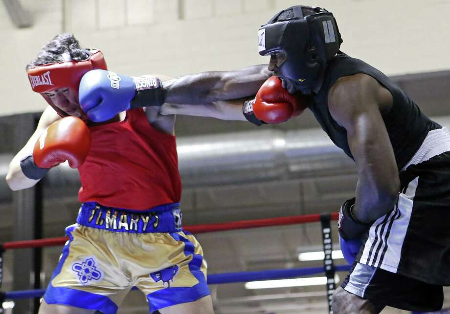 Luke Neftali Villafranca (left) and Terrence McKinney exchange punches during their light heavyweight championship bout in the semifinals of the 2016 San Antonio Regional Golden Gloves tournament on Feb. 26, 2016 at Woodlawn Gym. Photo: Edward A. Ornelas /San Antonio Express-News / © 2016 San Antonio Express-News