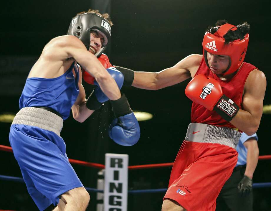 Johnny Moreno Jr. (left) is hit by Ramon Cardenas during their open bantamweight championship bout part of the 2015 San Antonio Regional Golden Gloves boxing tournament finals on Feb. 21, 2015 at the Scottish Rite Auditorium. Photo: Edward A. Ornelas /San Antonio Express-News / © 2015 San Antonio Express-News