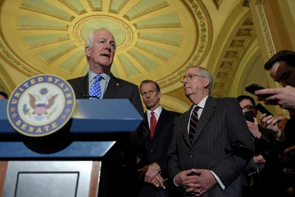 Senate Majority Whip John Cornyn of Texas, left, speaks to reporters during a news conference on Capitol Hill in Washington, Tuesday, Feb. 7, 2017. He is joined by Sen. John Thune, R-S.D., center, and Senate Majority Leader Mitch McConnell of Ky., right. (AP Photo/Susan Walsh)