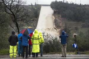 Department of Water Resources workers and members of the media watch as up to 20,000 cubic feet per second of water is released over the damaged spillway on Wednesday, Feb. 8, 2017 in Oroville, Calif. The Department of Water Resources said the erosion at Lake Oroville does not pose a threat to the earthen dam or public safety, and the reservoir has plenty of capacity to handle the continuing rain. (Randy Pench/The Sacramento Bee via AP)
