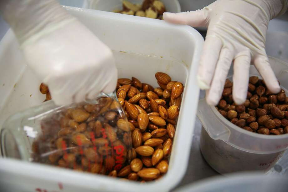 Prep chef Ana Barbara Can (center) scoops up a cup full of almonds to add to a blender while making almond milk at the Can Can Cleanse nut milk production facility in South San Francisco. Photo: Gabrielle Lurie, The Chronicle