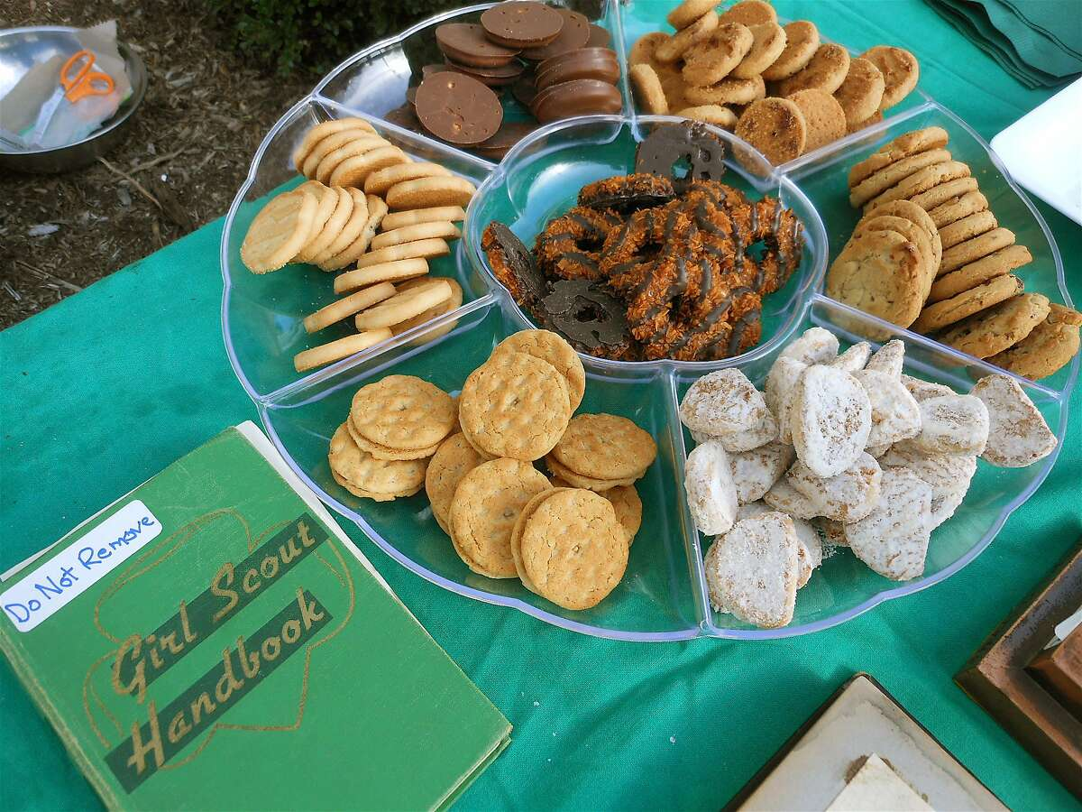 A Girl Scout handbook and trademark cookies on a table in front of Westport Town Hall, featured Monday at a centennial celebration of Scouting.