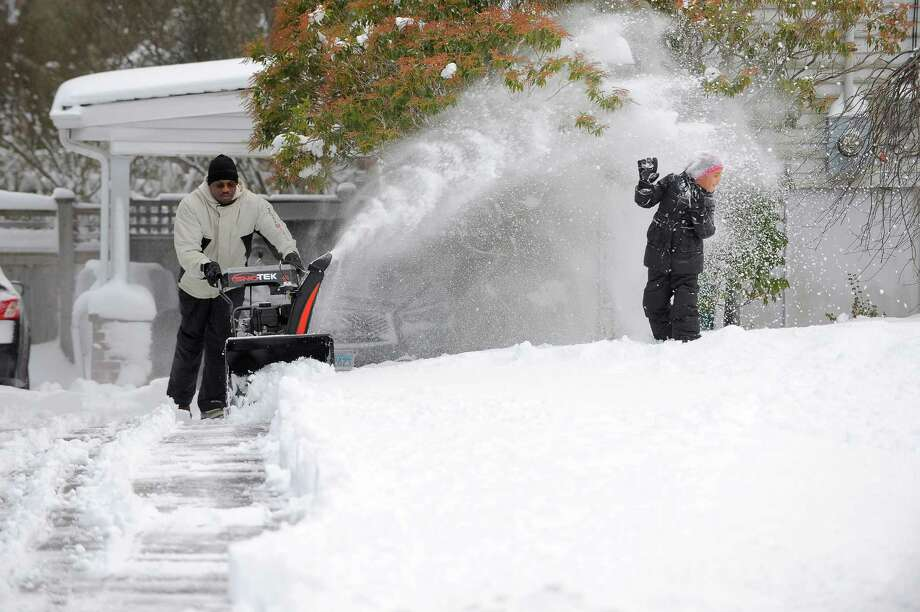 Olu Ajayi showers his daughter Olivia as he clears the driveway at his Brantwood Lane home in North Stamford on Feb. 9, 2017. The first significant snowfall for the 2017 Winter Season left 8-10 inches of winter mess for area residents to clen up. Photo: Matthew Brown, Hearst Connecticut Media / Stamford Advocate