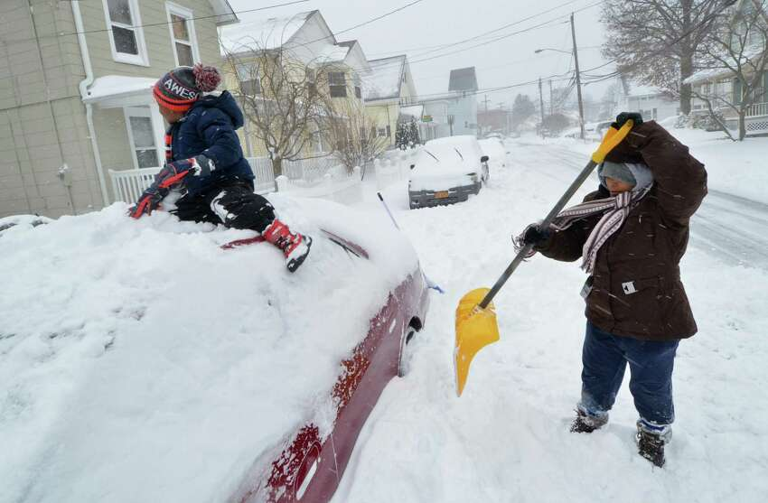 5 yr old Tramont Murray slides himself to the top of his Grandmother Hope Thomas' car while she digs it out as heavy snow falls on Thursday February 9, 2017 in Norwalk Conn