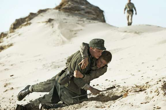 """German POWs, many of them teens, were charged with clearing Danish beaches of mines laid by Nazis during the war. Here, Helmut (Joel Basman, kneeling) and Sebastian (Louis Hoffman, diving) try to survive in the Oscar-nominated """"Land of Mine."""" Movie opens March 3. Photo courtesy Sony Pictures Classics."""