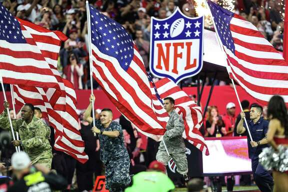 U.S. military personnel carry American flags as they run onto the field before Super Bowl LI at NRG Stadium on Sunday, Feb. 5, 2017, in Houston. ( Brett Coomer / Houston Chronicle )
