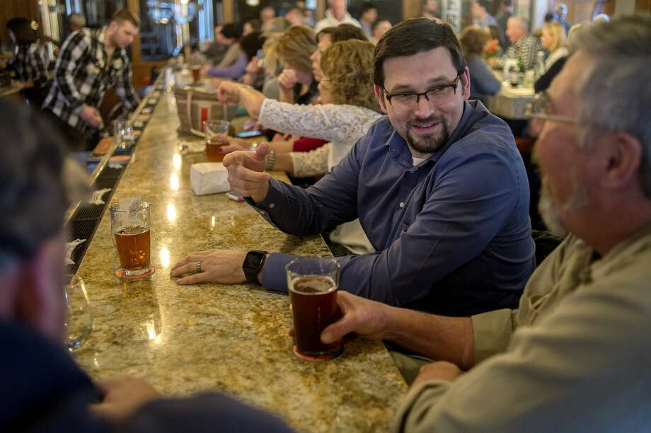 FILE — Steven Smith, left, of Midland chats with Randy Arthur of Hope Township while enjoying a beer during the grand opening of the Midland Brewing Co. Photo: Brittney Lohmiller/Midland Daily News/Brittney Lohmiller
