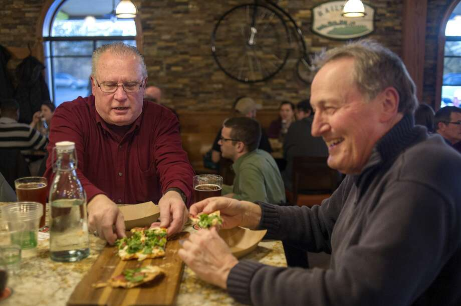 John McMillan, left, of Midland and Tom Meyer of Pinckney try the flatbread prosciutto during the grand opening of the Midland Brewing Co. Thursday evening. Hours will be 11 a.m. to 10 p.m. Monday through Thursday; 11 a.m. to midnight Friday and Saturday; and 10 a.m. to 5 p.m. Sunday. Midland Brewing is located at 5011 N. Saginaw Road. More than $1 million in upgrades were made to the microbrewery and full service kitchen. Out back, a beer garden and pavilion are set to open in May, connecting the brewery to the Pere Marquette Trail Rail-Trail. The entire facility will seat about 200. Photo: Brittney Lohmiller/Midland Daily News/Brittney Lohmiller