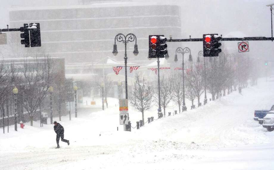 A pedestrian crosses the street at a lonely intersection in North Adams, Mass., during a winter storm Thursday. The storm dumped a foot or more of snow across areas of the New York-Boston corridor. Photo: Gillian Jones, MBI / The Berkshire Eagle