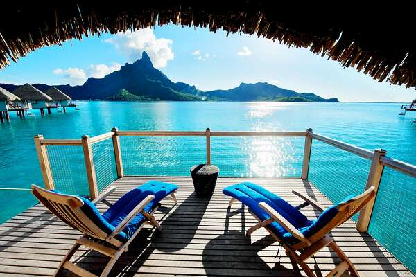 A bungalow terrace at Le Meridien Bora Bora overlooks crystal blue waters.